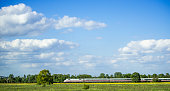 Train Moving By Grassy Landscape Against Sky