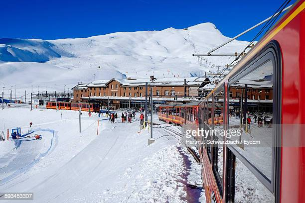 Train On Snow Covered Field By Alps Against Clear Sky