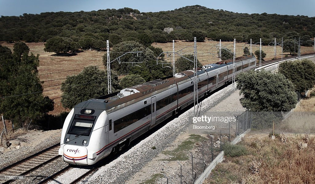 A train operated by Renfe Operadora SC travels beneath overhead power lines near El Escorial, in northern Madrid, Spain, on Sunday, Aug. 4, 2013. Spain's state-owned rail operator Renfe plans to cut almost 500 jobs, or 4% of staff, as early as this year, ABC reports, citing comments by Public Works Minister Ana Pastor. Photographer: Antonio Heredia/Bloomberg via Getty Images