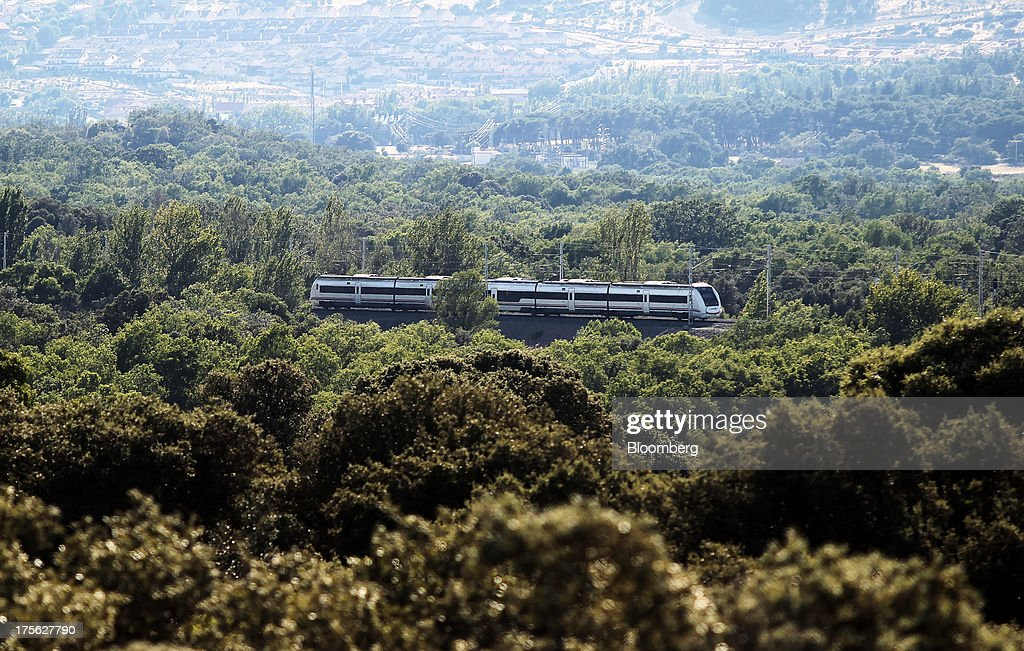 A train operated by Renfe Operadora SC travels past woodland near El Escorial, in northern Madrid, Spain, on Sunday, Aug. 4, 2013. Spain's state-owned rail operator Renfe plans to cut almost 500 jobs, or 4% of staff, as early as this year, ABC reports, citing comments by Public Works Minister Ana Pastor. Photographer: Antonio Heredia/Bloomberg via Getty Images
