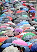 Train passengers shelter under umbrellas during a downpour as they queue outside a train station in Manila on August 26 2014 The weather bureau...
