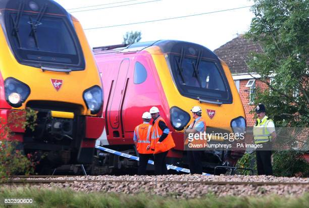 A train passes investigators and railway officials examining a train which collided with a car late Monday evening on the East Coast Main Line in the...