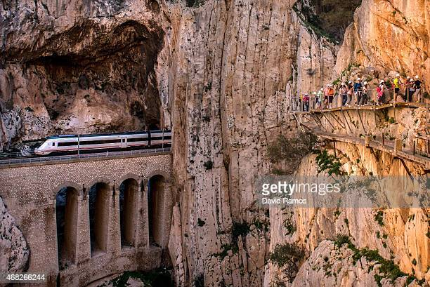 A train passes through a tunnel as tourists walk along the 'El Caminito del Rey' footpath on April 1 2015 in Malaga Spain 'El Caminito del Rey' which...