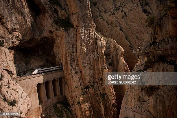 A train passes through a tunnel in the rocks as people walk the footpath 'El Caminito del Rey' a narrow walkway hanging and carved on the steep walls...