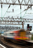 """A passenger train passing through a railway station at speed. Manchester Piccadilly, UK."""