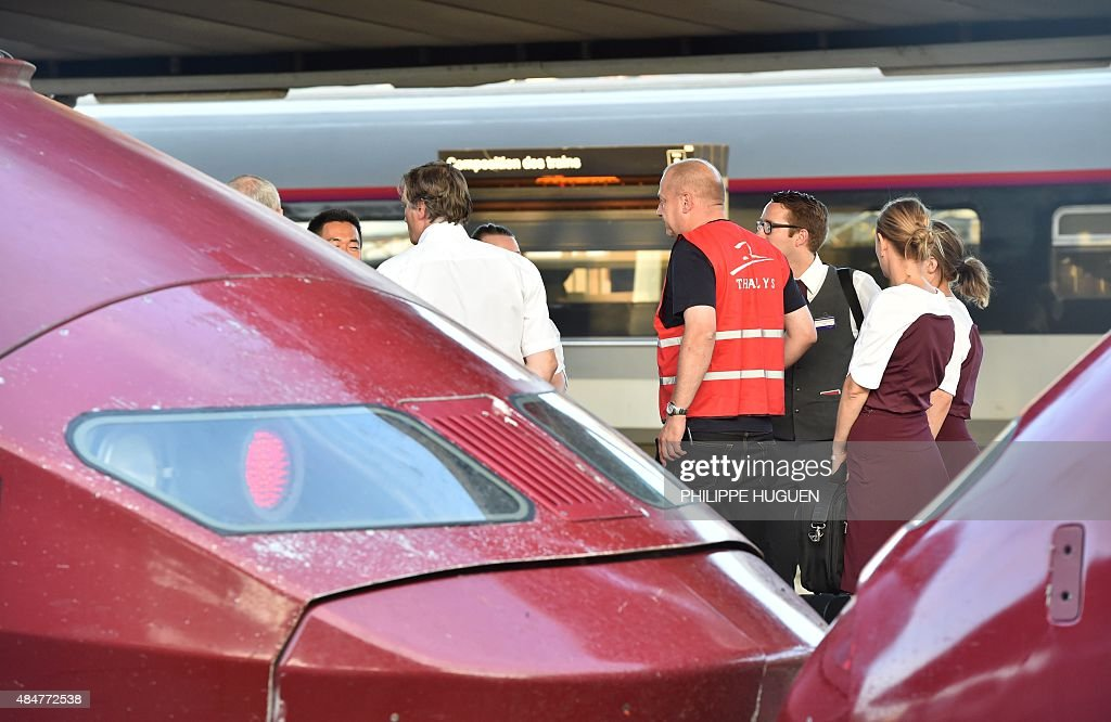 Train personnel of French national railway operator SNCF stand next to Thalys trains at the main train station in Arras northern France on August 21...