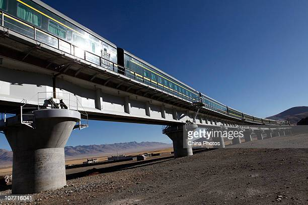 A train runs on a bridge through Shengen Village of Gongtang Town December 21 2010 in Damxung County of Tibet Autonomous Region China The 1956km...