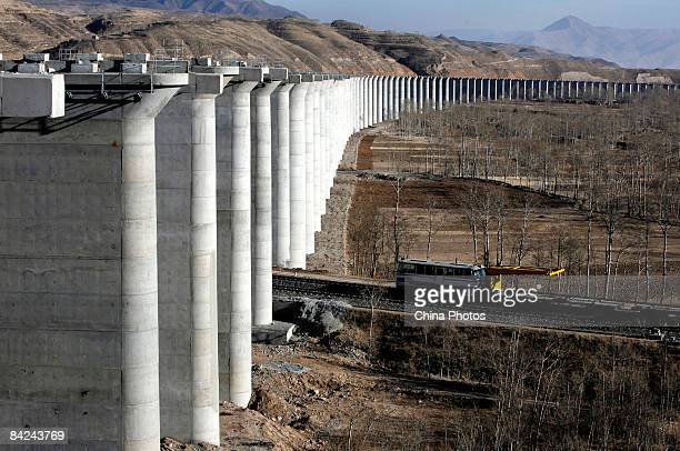A train runs past piers of a viaduct at the construction site of second phase of the QinghaiTibet railway from Xining to Golmud on January 11 2009 in...