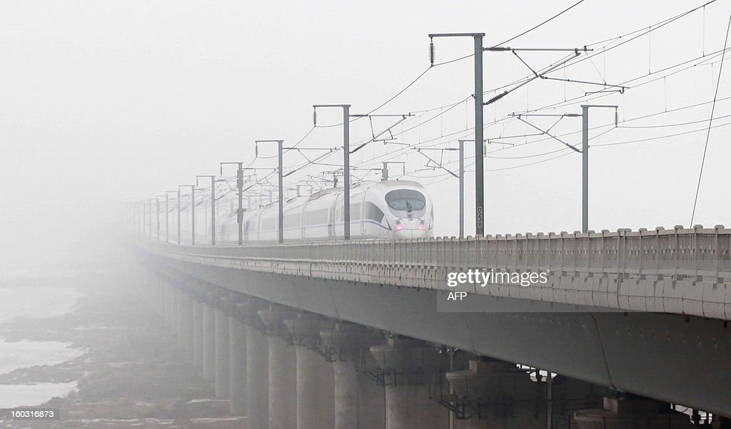 A train runs under heavy smog in Dalian, northeast China's Liaoning province on January 29, 2013. Residents across northern China battled through choking pollution on January 29, as air quality levels rose above index limits in Beijing amid warnings that the smog may not clear until January 31. CHINA OUT AFP PHOTO