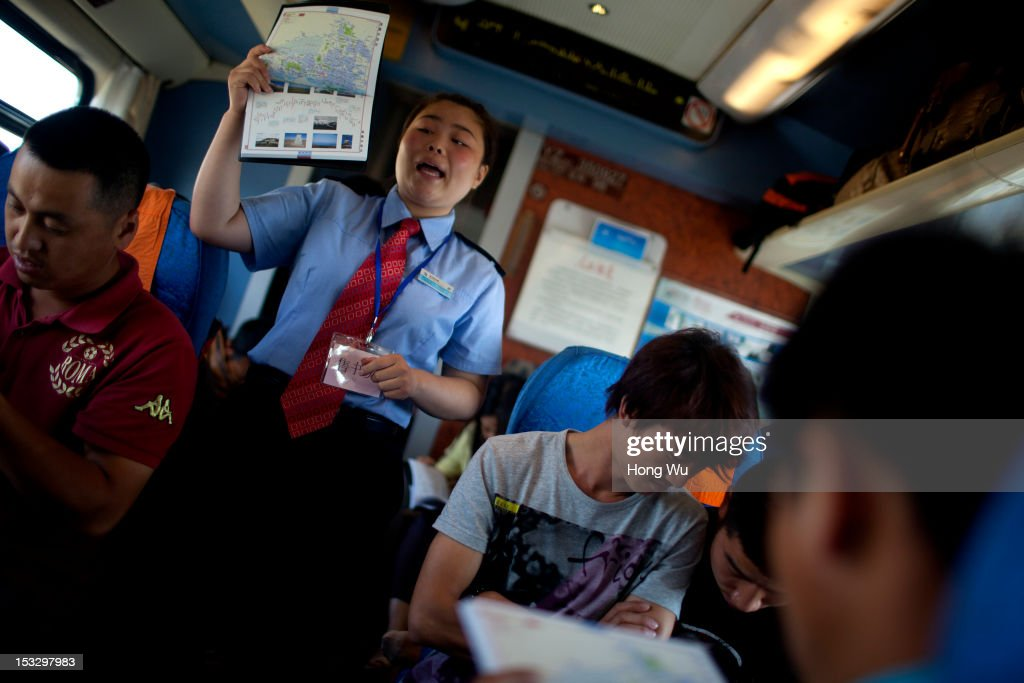A train staff promotes an atlas in a train carriage of from Beijing to Lhasa on August 14, 2012 in Baiyin, China. After Qinghai-Tibet Railway went into operation on July 1, 2006, connecting China's capital Beijing and Lhasa of Tibet Autonomous Region by 4,064 km of railway line. Passengers and supplies are transported by train on this the world's highest railway to Tibet.