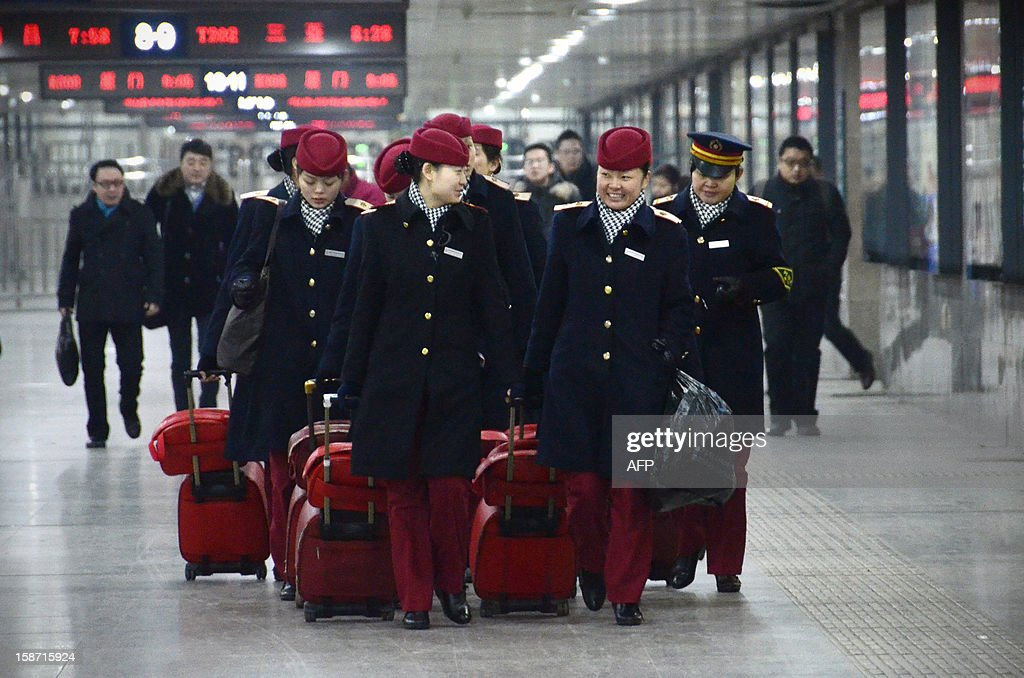 Train stewardesses make their way at the Beijing west railway station in Beijing on December 26, 2012. China on December 26 started service on the world's longest high-speed rail route, the latest milestone in the country's rapid and sometimes troubled super fast rail network. AFP PHOTO / WANG ZHAO