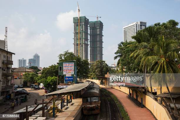 A train stops at a railway station as towers in the background stand under construction in the Fort neighborhood of Colombo Sri Lanka on Thursday...