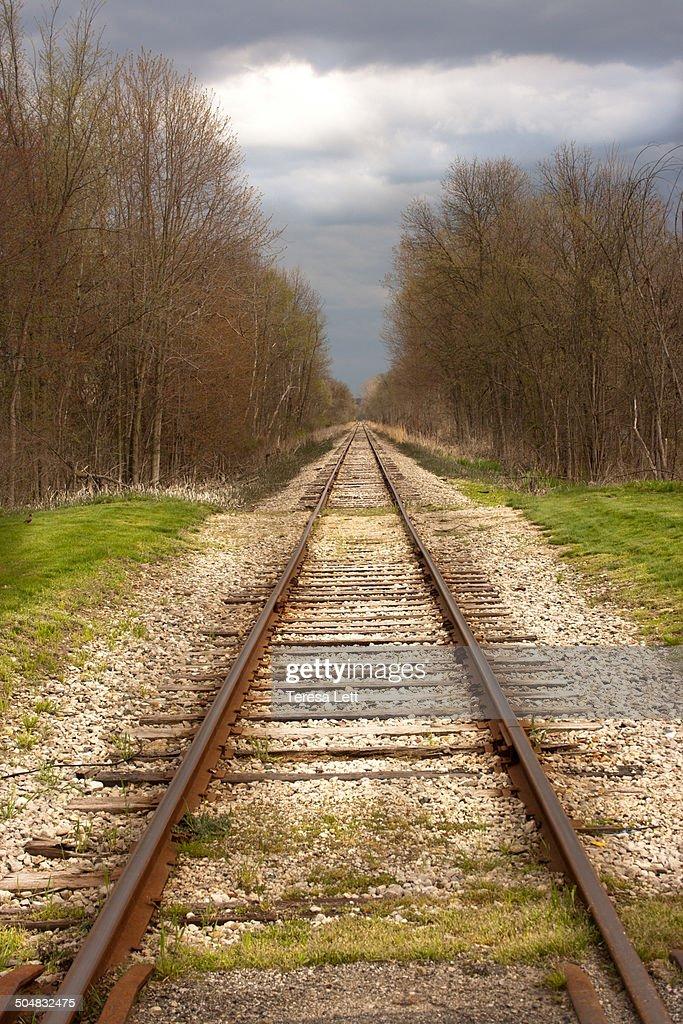 Train tracks under a stormy spring sky
