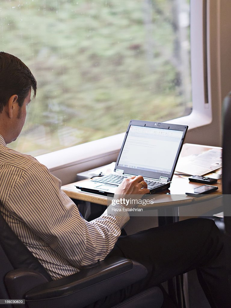 Train traveller works on laptop : Stock Photo