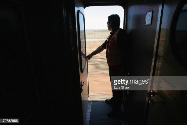 A train worker looks at the door as the Indian Pacific approach the Outback stop of Watson on the third day of the journey The Great Southern...
