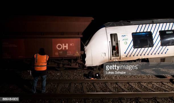 Train workers stand next to the wreckage of two trains that collided in MeerbueschOsterath district are seen on December 5 2017 in Dusseldorf Germany...