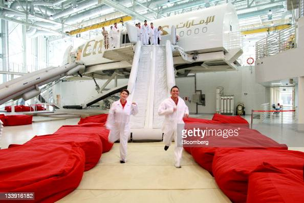Trainee aircrew for Emirates Airline practice an emergency exit using escape shoots on an aircraft simulator during a training session in the...