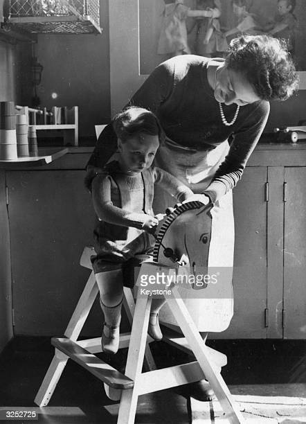 A trainee child care worker looking after a child at the Child Care Reserve HQ Piccadilly London formed by the National Council for Maternity and...
