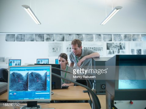 Trainee forensic scientists examining fingerprints on screens in laboratory