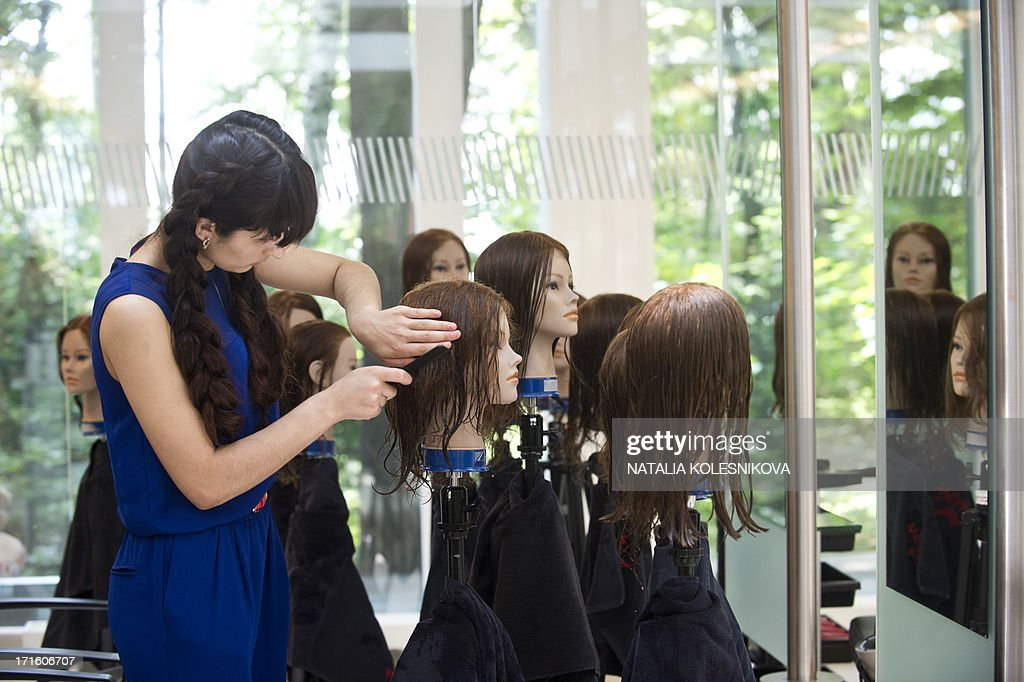 A trainee hairdresser practices on mannequin at an advanced classes for hair stylists in Moscow, on June 26, 2013.