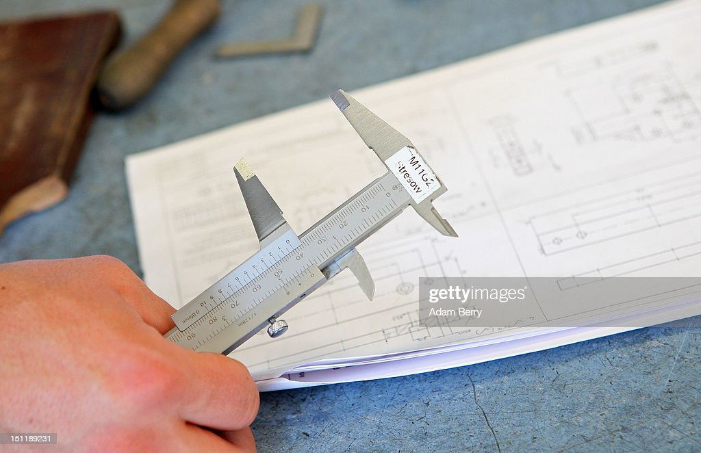 A trainee holds a caliper rule as he looks at technical plans for a project at a Siemens training center on September 3, 2012 in Berlin, Germany. Nearly 400 trainees began their apprenticeship training programs today at an in-house educational facility at the Siemens factory in Berlin.