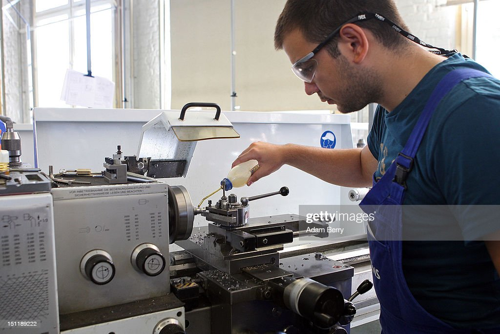 A trainee lubricates a turning machine at a Siemens training center on September 3, 2012 in Berlin, Germany. Nearly 400 trainees began their apprenticeship training programs today at an in-house educational facility at the Siemens factory in Berlin.