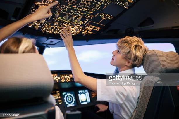 Trainee Pilot Adjusting Cockpit Switches, Guided By Her Instructor
