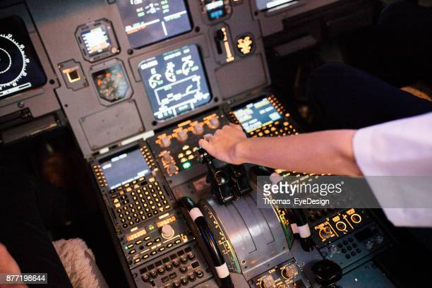Trainee Pilot With Her Hand On Throttle In Flight Simulator