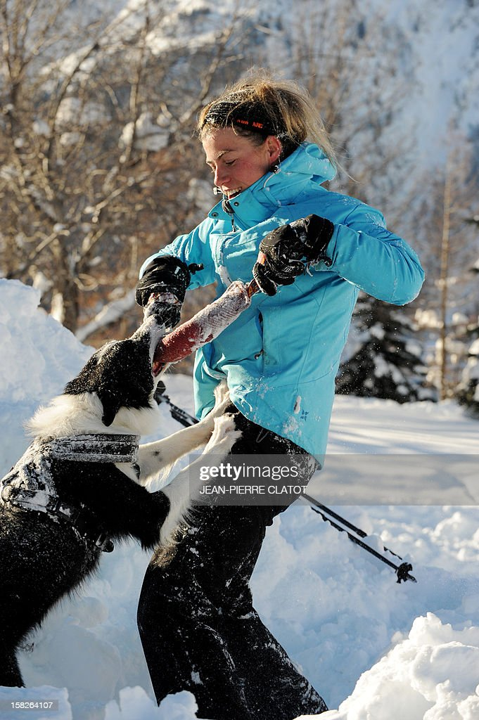 A trainee plays with an avalanche dog after the dog freed people buried in the snow, on December 11, 2012, during an avalanche dogs training session near Les Deux Alpes ski resort in the French Alps. France, with 140 avalanche rescue teams with dogs, is a reference in this activity sector which trains foreigners from Europe and other continents.