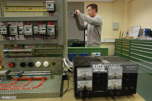 A trainee practices designing electronic circuit configurations during a visit by German Education Minister Johanna Wanka to the Ausbildungverbund...