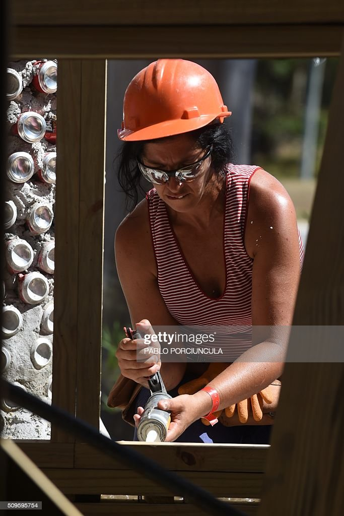 A trainee works during the construction of an auto-sustainable elementary school in Jaureguiberry -80 km east of Montevideo, Uruguay- on February 11, 2016. US architect Michael Reynolds, founder of Earthship Academy, gives training to 100 students from 30 countries (most of them architects) in Earthship design principles, construction methods and philosophy, to build the first school of this kind in the world. AFP PHOTO / PABLO PORCIUNCULA / AFP / PABLO PORCIUNCULA
