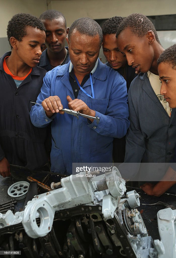 Trainees get instruction on assembling a car's motor in the automotive technology class at the AA Tegbare-id Polytechnic College on March 20, 2013 in Addis Ababa, Ethiopia. The AA Tegbare-id Polytechnic College is supported by Germany's KFW Development Bank and the GEZ as well as the Italian government. Ethiopia, with an estimated 91 million inhabitants, is the second most populated country in Africa and the per capita income is $1,200.