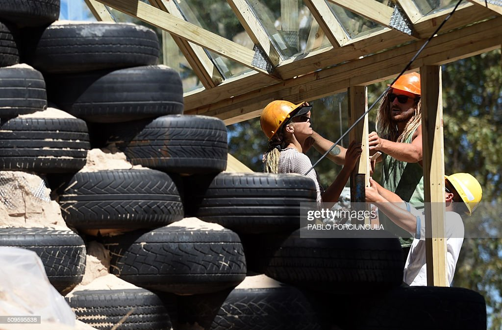 Trainees work during the construction of an auto-sustainable elementary school in Jaureguiberry -80 km east of Montevideo, Uruguay- on February 11, 2016. US architect Michael Reynolds, founder of Earthship Academy, gives training to 100 students from 30 countries (most of them architects) in Earthship design principles, construction methods and philosophy, to build the first school of this kind in the world. AFP PHOTO / PABLO PORCIUNCULA / AFP / PABLO PORCIUNCULA