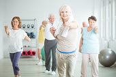 Smiling elderly trainer exercising with group of senior people at gym with equipment