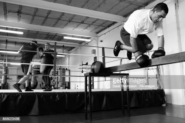 Trainer Anthony Farnell with boxer Tony Bellew as boxer Joe Selkirk jumps the bar during a training session at former WBU Middleweight Champion...