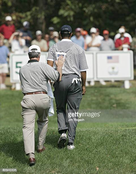 A trainer applies an ice pack to Tiger Woods' back during the second round of The Presidents Cup at Robert Trent Jones Golf Club in Prince William...