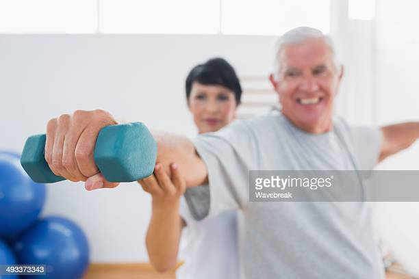 Trainer assisting senior man at gym