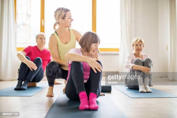 Trainer assisting senior woman in doing yoga