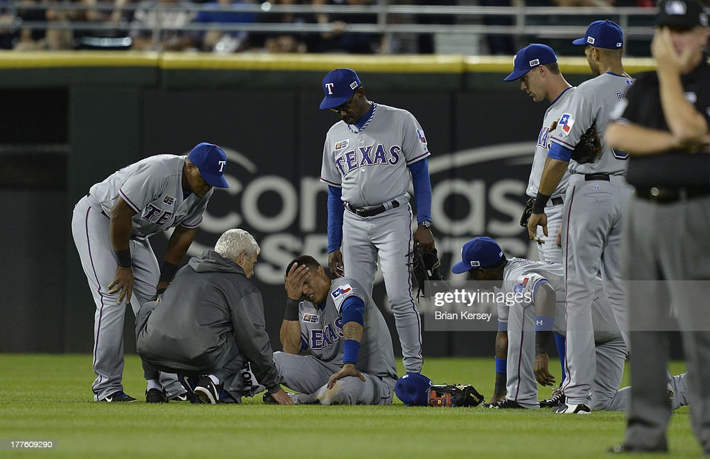 A trainer attends to center fielder Leonys Martin #2 of the Texas Rangers (C) as manager <a gi-track='captionPersonalityLinkClicked' href=/galleries/search?phrase=Ron+Washington&family=editorial&specificpeople=225012 ng-click='$event.stopPropagation()'>Ron Washington</a> #38 (C) and other teammates watch during the ninth inning of the 2013 Civil Rights Game against the Chicago White Sox at U.S. Cellular Field on August 24, 2013 in Chicago, Illinois. Martin was injured after colliding with left fielder David Murphy #7 while going for a fly ball. The White Sox won 3-2.