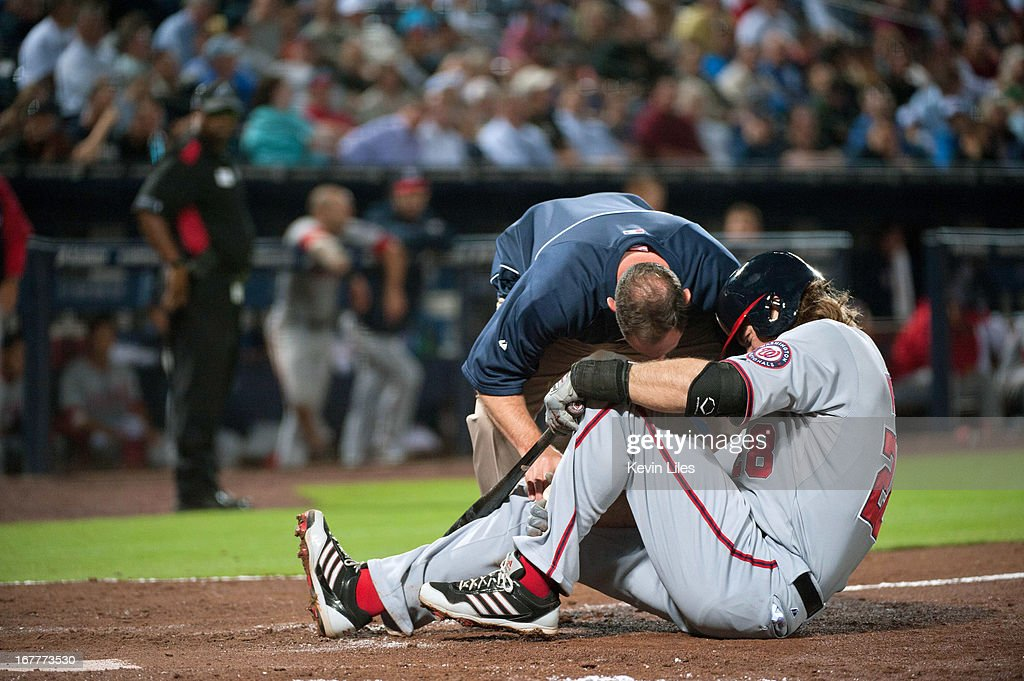 A trainer checks on Jayson Werth #28 of the Washington Nationals after he fouled a ball off his foot in the 8th inning against the Atlanta Braves at Turner Field on April 29, 2013 in Atlanta, Georgia. The Braves defeated the Nationals 3-2.