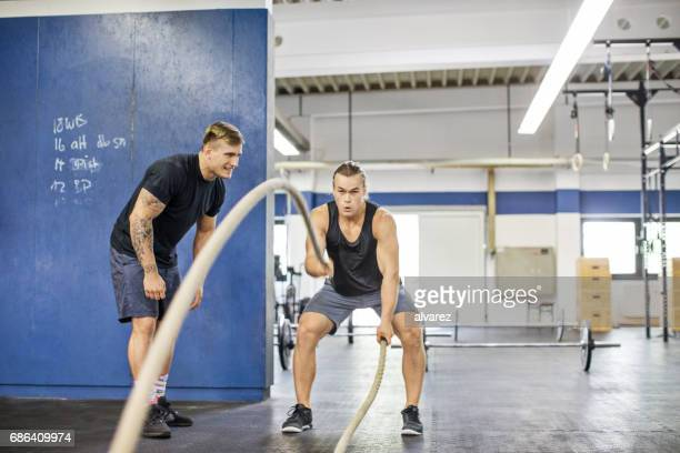 Trainer clapping for man exercising with ropes