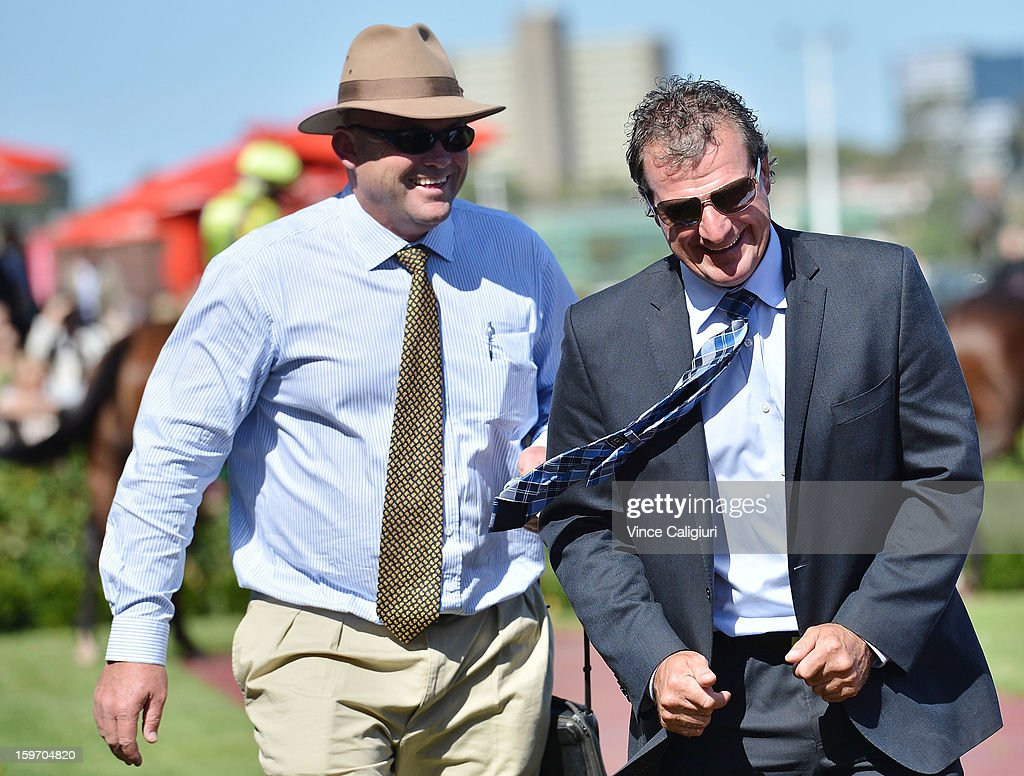 Trainer Darren Weir smiles with Peter Moody after a win by Lord of Brazil in the Craftsman Handicap during Melbourne racing at Flemington Racecourse on January 19, 2013 in Melbourne, Australia.