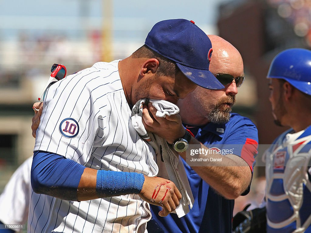 Trainer Ed Halbur of the Chicago Cubs helps Aramis Ramirez off of the field after Ramirez was hit in the mouth by the ball against the Houston Astros...