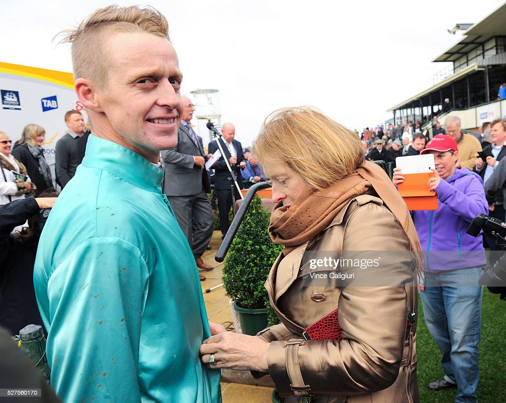 Trainer <a gi-track='captionPersonalityLinkClicked' href=/galleries/search?phrase=Gai+Waterhouse&family=editorial&specificpeople=239456 ng-click='$event.stopPropagation()'>Gai Waterhouse</a> helps jockey Brad McLean with his silks before the presentation after Valediction won Race 6, the Brierly Steeplechase during Brierly Day at Warrnambool Race Club on May 3, 2016 in Warrnambool, Australia.