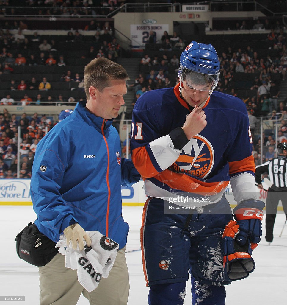 Trainer Garrett Timms walks John Tavares #91 of the New York Islanders off the ice after his injury in the game against the Dallas Stars at the Nassau Coliseum on October 9, 2010 in Uniondale, New York. The Stars defeated the Islanders 5-4 in the shootout.