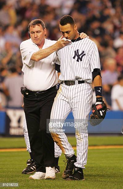 Trainer Gene Monihan helps Derek Jeter of the New York Yankees off the field after he made a diving catch in the 12th inning of their game against...
