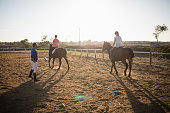 Trainer guiding young women in riding horse at barn