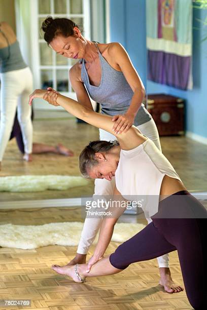 Trainer helping client stretch