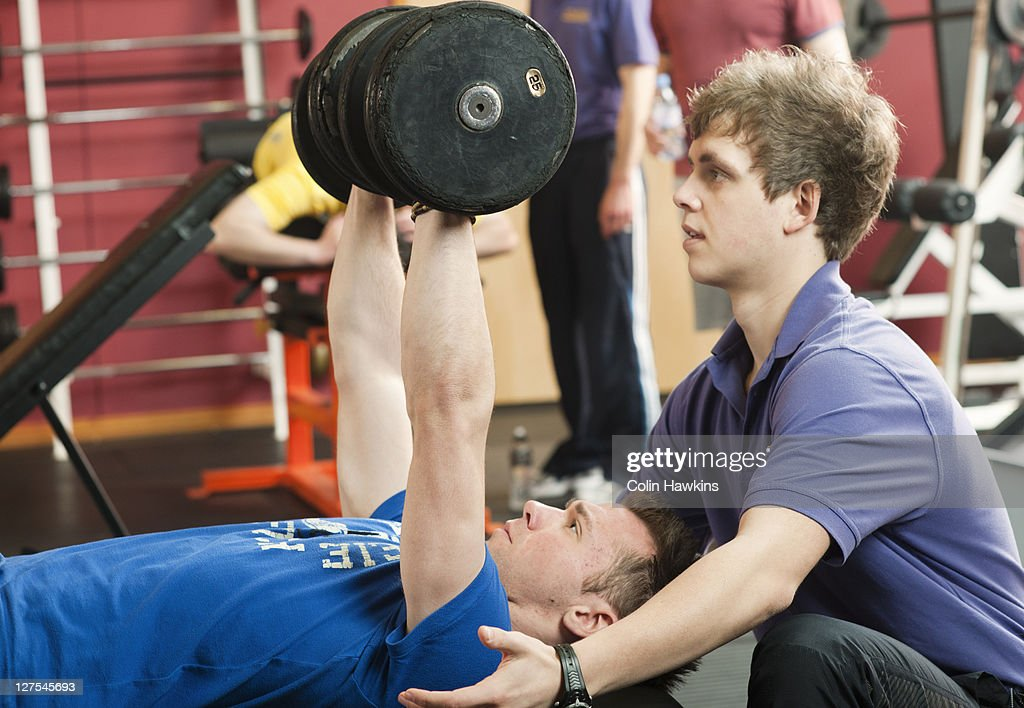 Trainer helping man lift weights at gym : Stock Photo