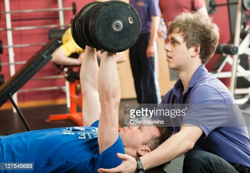 Trainer helping man lift weights at gym : Photo